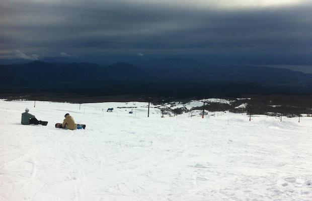 Praticantes de snowboard param na descida na neve do vulcão Villarica