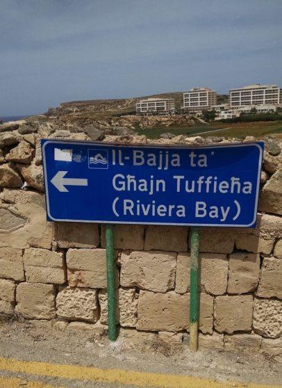 Placa indicando praias em Malta. A segunda praia, como tem outro nome em inglês, tem a tradução abaixo