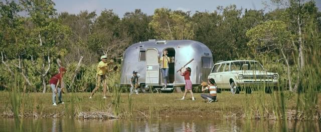 Perhe ulkoilee järven rannalla, 60-luvun asuntovaunun edessä.
