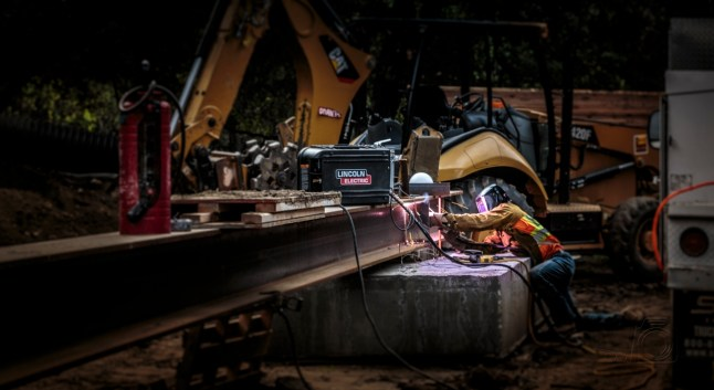 welder kneeling while arc welding