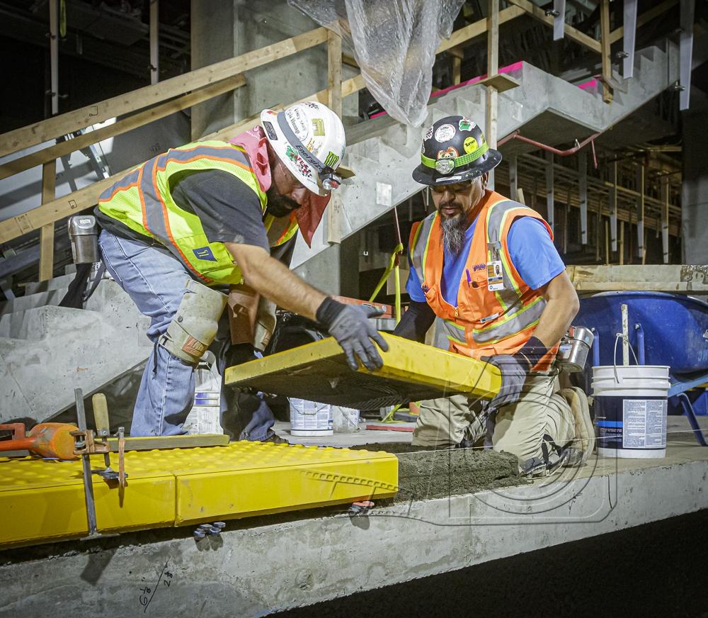 men installing yellow concrete block