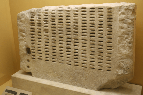 Large stone with columns of slots carved into it - a kleroterion