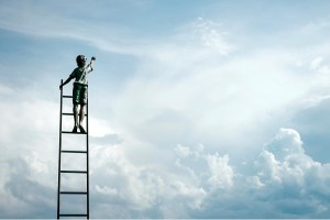 Young boy on top of ladder reaching for the sun