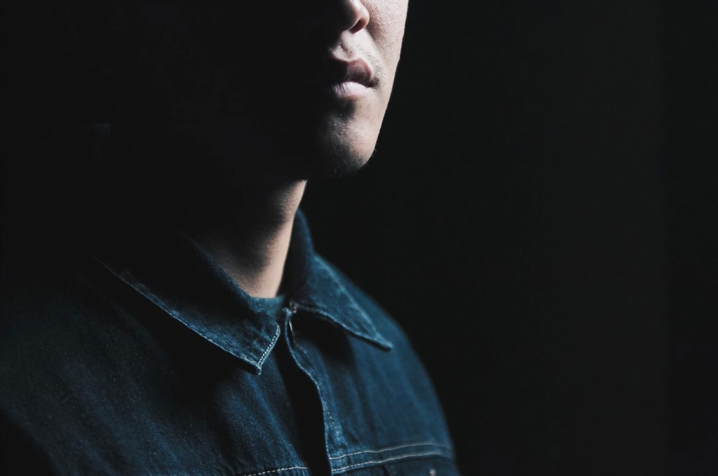 partial image of young man emerging out of dark background