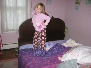 bed breaker :: 5 year old daughter standing on bed with antique bed frame