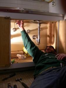 man working on under sink plumbing
