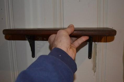 tiny wood shelf with cast metal brackets
