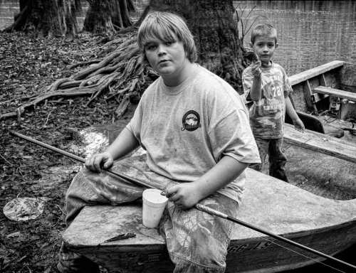 HONORABLE MENTION | Mike Nalley Baiting is an image I made on one of my many trips to Apalachicola Bay to document the oyster and fishing culture. We were at Smith Creek in the Apalachicola National Forest visiting some oystermen and their families on opening day of squirrel season. We found their camp and everyone was enjoying the midday around camp. I just walked around talking and photographing the oystermen and their kids. These two were fishing and playing around the creek when I walked up and got this shot. This is still one of my favorite images made around the bay. BIO: Mike has been photographing since 1974 where it all started as a hobby. He studied photography at the Art Institute of Atlanta where he has an Associate Degree in Photography. He owned and operated a studio in Marietta, GA until 1985 when life got the best of his photography work. Mike became active again in the art world in 2006 when the urge to photograph grabbed him once again. He has worked prolifically in digital ever since. He has spent the last 6 years documenting the oyster and fishing culture in the Apalachicola Bay area of Florida. Over the years he has made some wonderful friends and made some great photographs of the oystermen and women, fishermen and seafood workers in the area. Mike has won many awards over the years. He has exhibited all over the Southeast and can be found most days rambling with his camera in hand in search of that one more subject. ©Mike Nalley