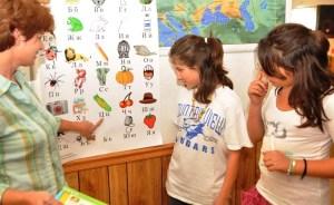 """Учителката Живка Костова (ляво) показва буквите на Вивиан и Памела в българското училище в Ел Ей """"Иван Вазов"""". Вивиан Неделчев (в средата) е избрана от """"Националната общество за надарени и талантливи"""" за едно от най-успешните деца на САЩ за нейната възраст. Снимка: Училище"""
