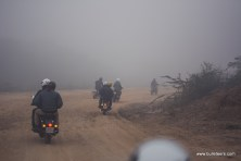 Bulleteers riding their royal enfield motorcycles in fog on the way to Holipura