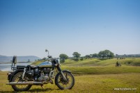 a royal enfield classic 500 parked in grasslands of pagara. a continental gt and rest of the group and can be seen in the background