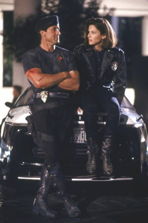 UNSPECIFIED - AUGUST 02: Full shot of Sylvester Stallone as John Spartan wearing police uniform and hat/cap, standing beside Sandra Bullock as Lenina Huxley, sitting on hood of car. (Photo by Andrew Cooper/Warner Bros./Getty Images)