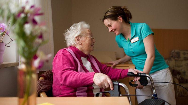 Eine Pflegerin hilft einer alten Dame.