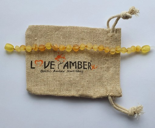 Raw honey amber anklet laid out straight on a small hessian bag