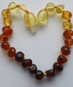 Polished rainbow amber anklet arranged into a heart