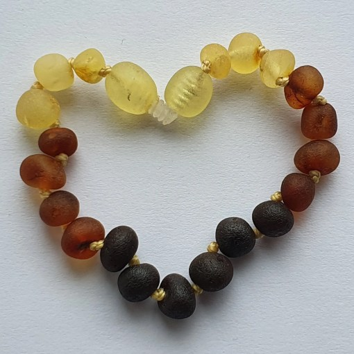 Raw rainbow amber anklet arranged into a heart