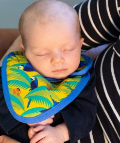 Milk-drunk newborn snoozing in a brightly patterned bib after a feed