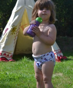 Toddler in a reusable nappy drinking water outside a tent