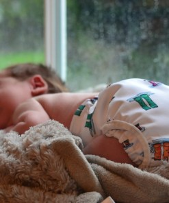 Newborn baby asleep on a blanket in front of a window, wearing nothing but a resuable nappy in a welly print