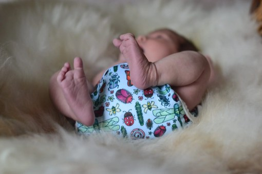 Newborn baby asleep on a faux-sheepskin rug wearing nothing but a resuable nappy with a bugs design