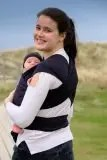 Woman carrying baby in a black stretchy wrap looking back over her shoulder