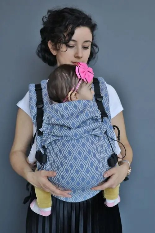 Woman carrying a baby in a Neko Switch Lycia Ayaz