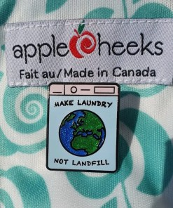 Make Laundry Not Landfill pin badge against an Applecheeks nappy