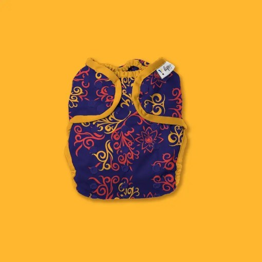 Hippynut nappy in deep purple-blue background with elaborate swirl design in yellow and coral