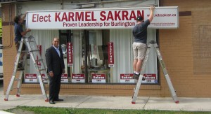 Liberal candidate Karmel Sakran stands proudly before the sign being installed outside his campaign office on Guelph Line