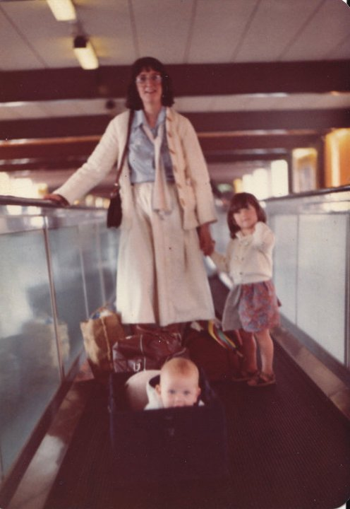 Baby in a carrycot, toddler and me on a travelator at Heathrow