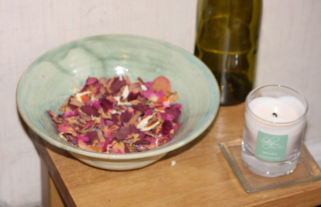a bowl of pot pourri and a candle