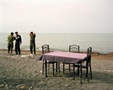 Two Azeri guards talk to a local man at a beach cafè in Lankaran, Azerbaijan.