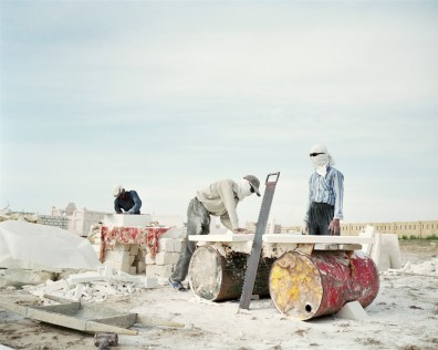 In a coastal cemetary, Uzbek migrant workers build elaborate mausoleums for the new oil rich middle class. They wear makeshift masks and sunglasses to protect themselves from the sun's glare, which bouces off the mussel-chalk they work with.