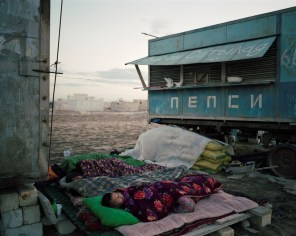 Sunrise in Koshkar-Ata cemetary, Kazakhstan. A group of ten Uzbek men live inside the necopolis for the duration of summer. They rarely leave the site, working from dawn till dusk, and sleeping on palattes in the open air.