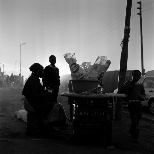 A street vendor in Diepsloot sells her wares early in the morning as people make their way to work and school.