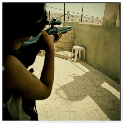 Palestinian boy from Wadi Fuqin Aiming a toy gun at the Beitar Ilit Settelment.