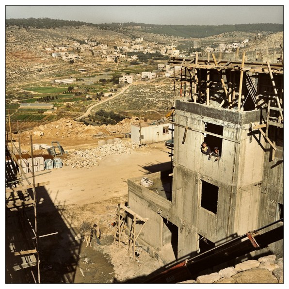 Palestinian workers at the settelment construction site. In the background, the village of Wadi Fuqin.