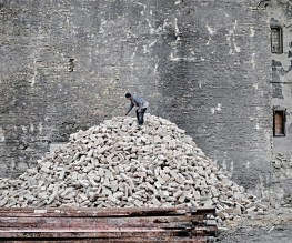 A man sorts out bricks of a demolished building on the outskirts of Budapest. Like many of his fellow citizens in small villages he regularly goes to the capital to find some casual work.