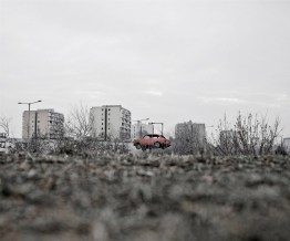 A car wreck on a pole is advertising a scrapyard close to some blocks of flats on the periphery of Budapest. Twenty percent of the Hungarian population live in such buildings mainly on the outskirts of major cities.
