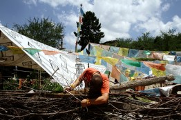 A Tibetan man adjusts prayer flags outside his home, located on the eastern fringes of the Qinghai-Tibetan Plateau. Traditionally, Tibetan people of the region have sustainably used the forests, however increased developments in the region have seen more and more forests felled for use in local industry.