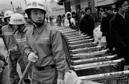 Firefighters shovel snow at a shopping mall in Changsha, China 2008. During the crippling winter storms of 2008 public resources were heavily allocated towards symbolic gestures of civic aid with little practical effect.