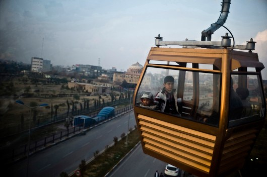 Cable car in Kurdistan. ERBIL, Iraq: Fri 28th Jan 2011: A cable car carries a family over the city of Erbil in Iraq's semi-autonomous Kurdish north. Long the safest and most accessible city in Iraq, Kurdish Erbil is awash with new housing developments and foreign investors. A four bed-room home can set you back as much as $500,000.
