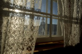 A church is seen through a window on the site of Fort Chipewyan's Residential School.