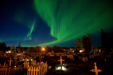 The Northern Lights are seen over Fort Chipewyan's main cemetery. The site is now overflowing with new graves and will soon need to be expanded.