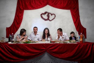 """Artak Petrosyan and his bride Armine Baghdasaryan sit at the main table during the evening reception in Khtsaberd village hall. The young couple will receive a wedding payment of approximately €575 (300,00 ad) as part of the government's """"Birth Encouragement Program"""". Khtsaberd village, Hadrut Region, Nagorno Karabakh, 16th July 2011."""