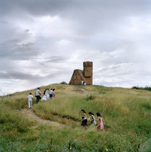 """A wedding party visits the """"Grandmother and Grandfather"""" monument in Stepanakert, for a traditional photoshoot by the country's national symbol. The newlyweds will receive a wedding payment of approximately €575 (300,00 ad) as part of the government's """"Birth Encouragement Program"""". Nagorno Karabakh, 2011."""