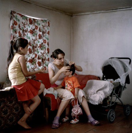 """19 year old Narine Hakobyan combs her 2 year old daughter Angelina's hair at home in Kolatak village, where she lives with her husbands family, including her young sister-in-law, Lilit (left). Nagorno Karabakh, 2011. Narine and her husband Suren have received approximately €1150 (600,00 ad) in wedding and baby payments as part of the government's """"Birth Encouragement Program""""."""