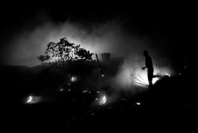 VENEZUELA, SANTA ELENA DE UAIREN. JANUARY 2010. A man walking through a forest fire. Once an area is deforested the easier and fastest way to clean the land is burning everything with a fire.