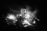 Pakistan, Rawalpindi District March 2009: a man standing up on a burning amount of garbage.
