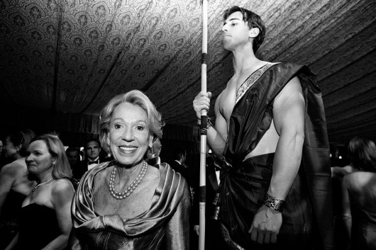 """Socialite Charlotte Shultz walks past a model dressed as a temple guard from """"Samson and Delilah,"""" the opera being performed that night, during the San Francisco Opera Opening Night Gala."""